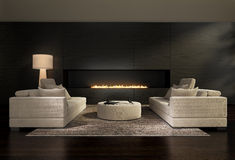 Dark contemporary interior, a living room with a flat gas fireplace