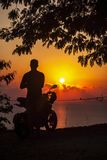 Dark contour of a motorcycle and a man at sea sunset royalty free stock image