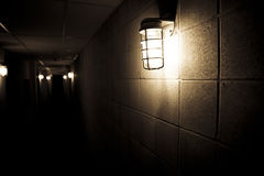 Dark corridor. A dark building alley with only a few light bulbs fixed on the concrete walls to provide a little bit of light. The corridor seems to end in Stock Images