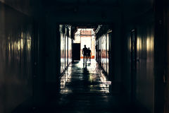 Dark corridor in building, doors and silhouettes of two man, perspective Royalty Free Stock Photo