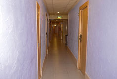 A Dark Corridor. A long dimly lit corridor in a hotel Royalty Free Stock Images