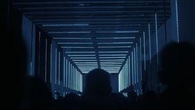 People in dark corridor with neon lights. Dark corridor with neon beaming lights, leads to bright screen, full of obedient and passive people, negative view of stock video footage