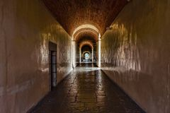 Dark corridor with pale yellow walls in an old palace Stock Photo