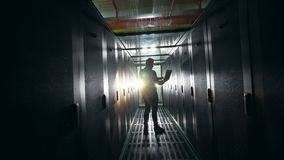 Dark corridor of the server room with an IT specialist in it. 4K stock video footage