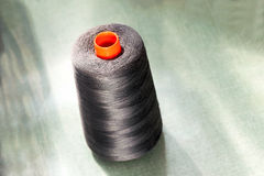 Dark cotton thread on an orange upright spool Stock Images