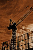 Dark Crane. Silhouette of a heavy lifting crane constructing an office block. Surrounded by scaffolding with wispy clouds in the sky Royalty Free Stock Photos