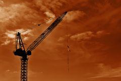 Dark Crane With Wispy Clouds. A Crane on the sky line with flags flying from its wire Stock Images