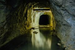 Dark creepy dirty flooded abandoned mine tunnel.  royalty free stock images