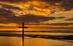 Three Bird of Salvation. Dark cross on a beach with a wonderful sunset sky ad three sea birds flying over Stock Image