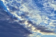 Dark Cumulus and light feathery clouds on the blue sky. Cumulus clouds are on the diagonal. From left looming rain cloud. On the right is a clear sky with Stock Photography