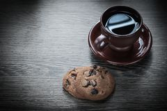 Dark cup of coffee saucer on wooden board cookies Stock Photos