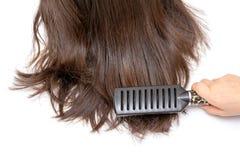Dark curls brushing comb isolated on white stock image
