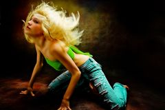 Dark dance. Blond woman in dance position on dark background stock image