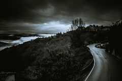 Dark and dangerous road in the clouds - black and white. View from Perugia Italy - black and white, road in the clouds Royalty Free Stock Image
