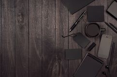 Dark deluxe black blank stationery, mockup scene with phone, coffee on black wooden plank, blank objects for placing your design. Modern stylish work place Royalty Free Stock Image