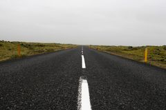 On a dark desert highway. Straight road heading off into the distance Royalty Free Stock Image