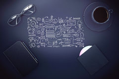 Dark desktop with business sketch. Top view of dark office desktop with business sketch, notepad, coffee cup, glasses and other items Royalty Free Stock Images