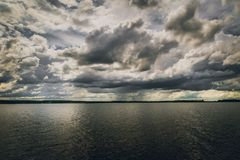 Dark and detailed sky above the water stock image