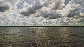 Dark and detailed sky above the water stock photo