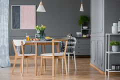Dark dining room interior. Pink and navy blue painting in dark dining room interior with wooden table and chairs Stock Images