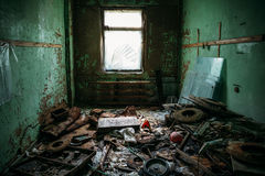 Dark dirty room with garbage in an abandoned industrial building. Toned Royalty Free Stock Images