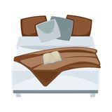 Dark double bed with pillows and open book in bedroom Stock Image