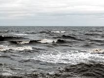 Dark dramatic seascape with breaking waves in stormy weather Royalty Free Stock Image