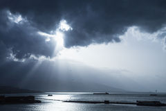 Dark dramatic sky with sunlight rays over sea. Blue toned photo filter effect royalty free stock photo