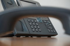 Dark earphone (receiver) with a corporate business landline telephone in the background. Dark receiver with a corporate business landline telephone in the Stock Photo