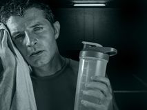 Dark edgy portrait of young sweaty tired and exhausted sport man with water bottle cooling off after hard fitness workout at gym royalty free stock photography