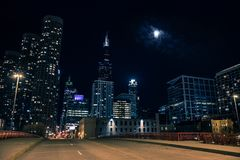 Dark and eerie Chicago city street bridge night scene. With the Sears Willis Tower skyscraper and the moon stock image