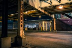 Dark and eerie Chicago urban city street night scenery. With elevated CTA train tracks, vintage industrial warehouses and factories royalty free stock photography