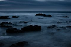A dark eerie seascape. With rocks Royalty Free Stock Image