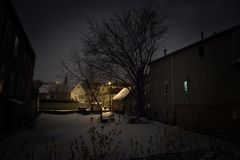 Dark and eerie snow filled empty lot at night. Royalty Free Stock Photo