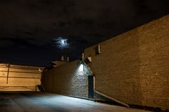 Dark city alley at night. Dark and eerie urban city alley with the moon at night Royalty Free Stock Image