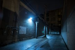Dark and eerie urban city alley at night. royalty free stock photo