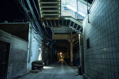 Dark and eerie urban city alley at night royalty free stock photos