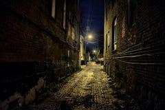 Dark and eerie urban city cobblestone brick alley at night. Dark and eerie urban city cobblestone brick paved alley at night royalty free stock photo