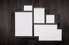 Dark elegance working space with blank notepad, letterhead, business card, coffee cup and earphone on black wood plank background.