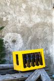 Dark Empty Beer Bootle in Yellow Case Box on Wood Pieces at Outside in Front of Cement Wall. Outside royalty free stock photography