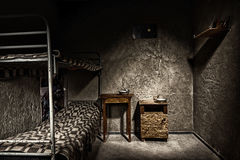 Dark empty jail cell with iron bunk bed and wooden bedside table Royalty Free Stock Photography