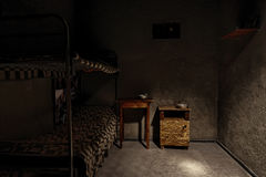 A dark empty prison cell with iron bunk bed and bedside table Royalty Free Stock Image