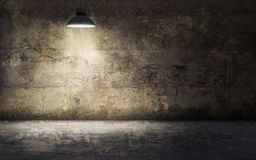 Dark empty room with old damaged concrete wall and ceiling lamp. Shining royalty free stock photography