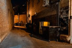 Dark empty scary urban city street alley at night. Dark empty scary urban city street alley with dumpsters and vintage buildings at night Stock Photography