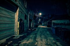 Dark empty and scary urban city street alley at night. Dark empty and scary urban city street alley with vintage buildings and garbage cans at night Stock Images