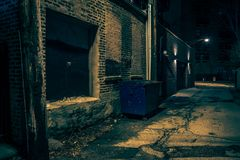 Dark empty and scary urban city street alley at night. Dark empty and scary urban city street alley with a vintage warehouse loading dock and a garbage dumpster Royalty Free Stock Image