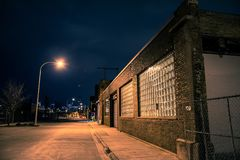 Dark empty and scary urban city street at night. Dark empty and scary urban city street road with alleys and vintage industrial factory and warehouse buildings Royalty Free Stock Image