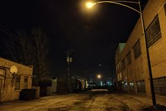 Dark empty and scary urban city street road at night. Dark empty and scary urban city street road with alleys and vintage industrial factory and warehouse Stock Photography