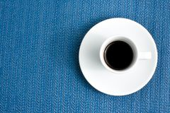 Dark espresso in a cup on blue texture Stock Photo