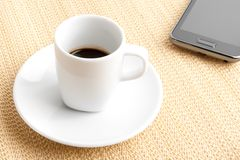 Dark espresso in a cup near smartphone Stock Photos